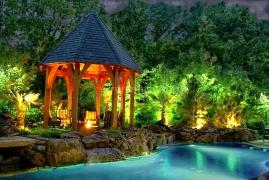 Наружное освещение на участке с деревянной беседкой и искусственным водоемом